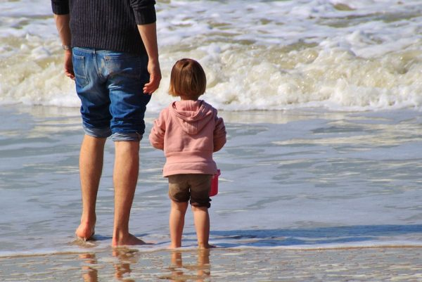 A father and child paddling in the sea