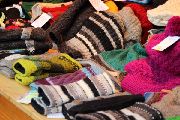 A table full of colourful hats and gloves