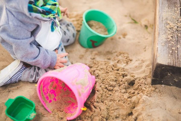 Little boy with buckets in the sand