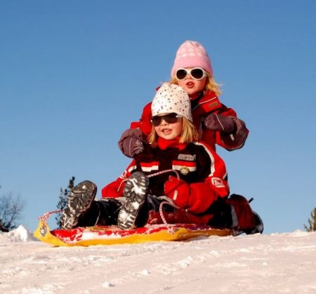 Two girls on a sled on the snow
