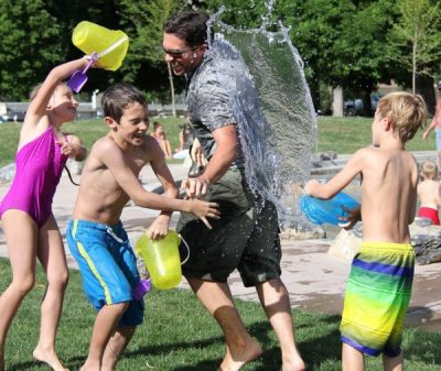 A family having a water fight outdoors