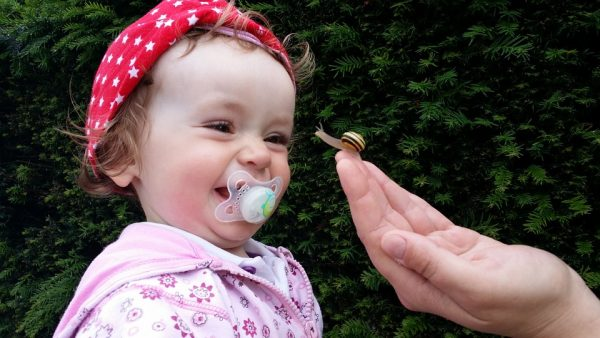 A little girl with a pacifier laughing at a snail