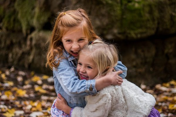 Two little girls hugging and laughing outside