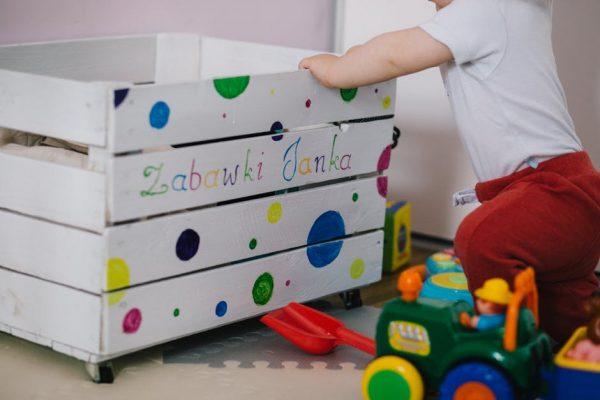 A little boy reaching into a toy box
