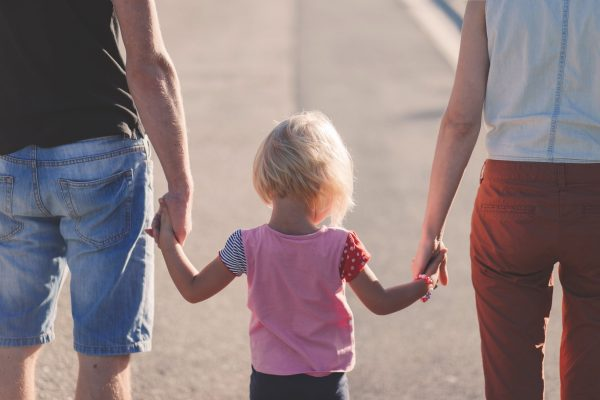 A little girl holding her parents' hands