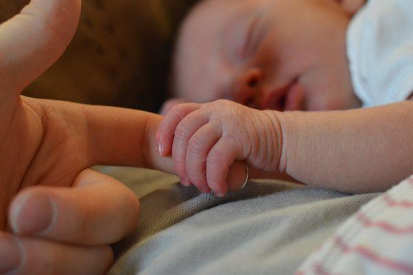 A newborn sleeping and holding his mother's finger