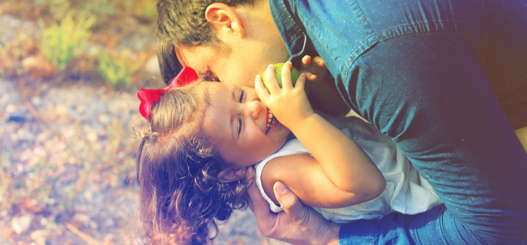 A father kissing his daughter on the cheek