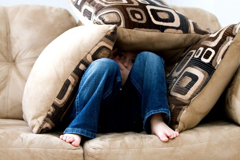 A little girl hiding under pillows