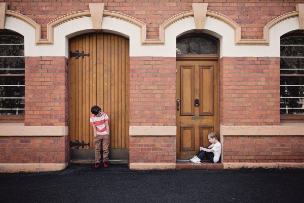 Two boys standing and sitting in front of two doors
