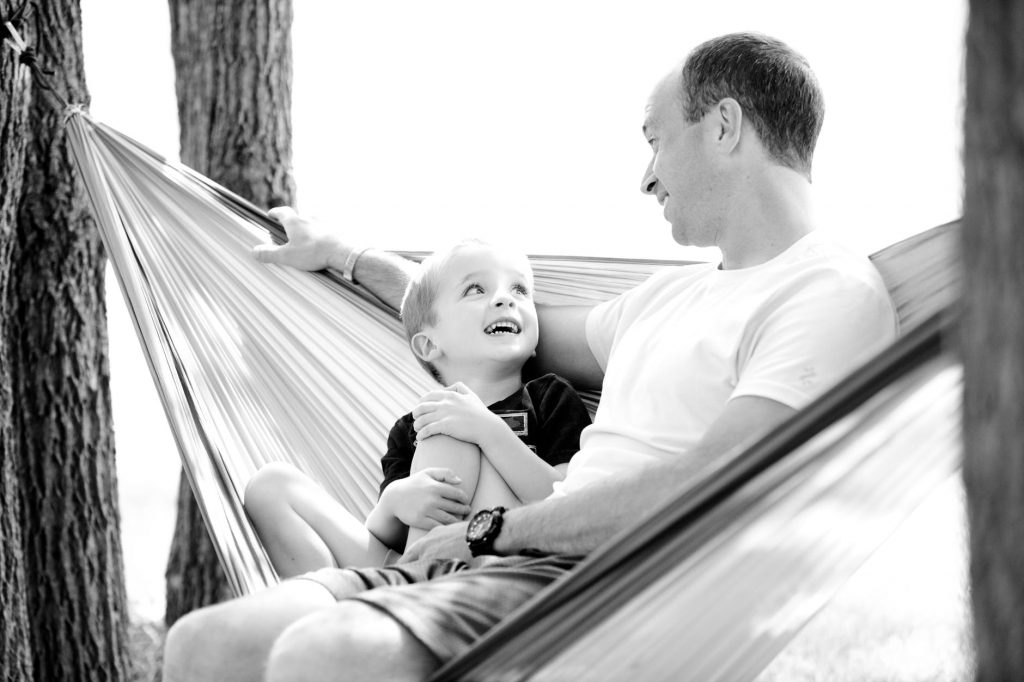 A dad talking to his son on a hammock