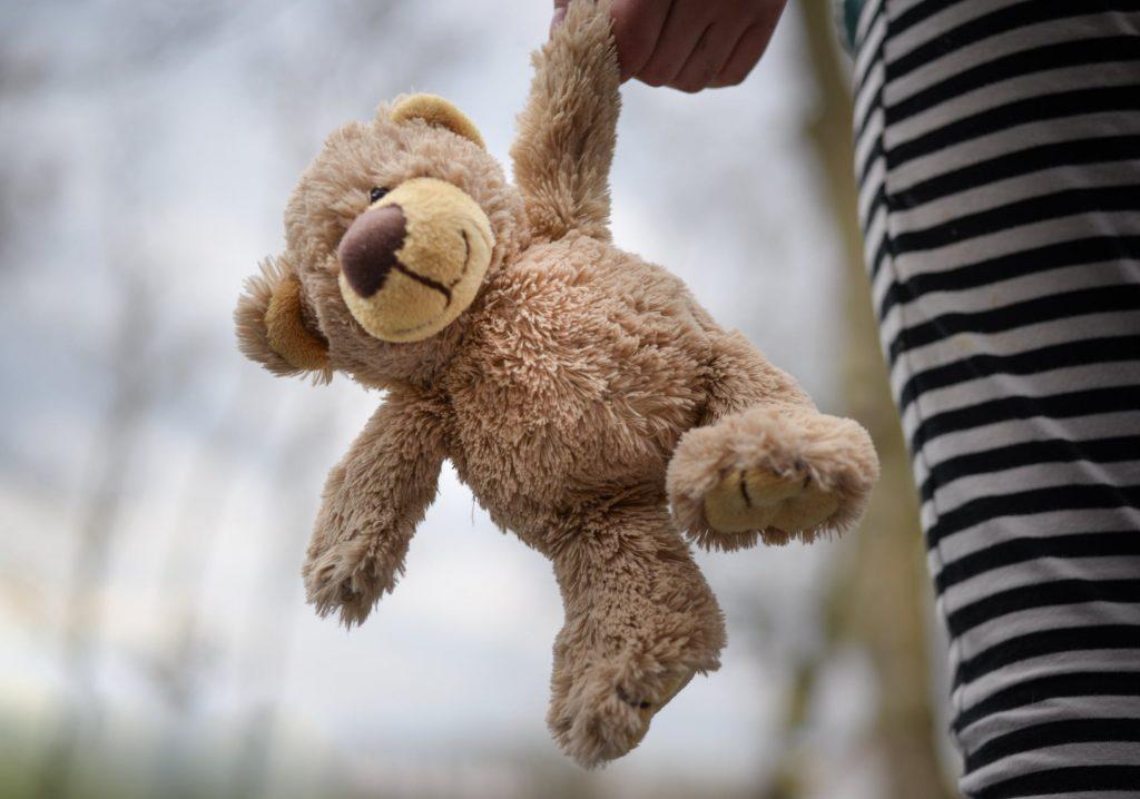 A child and their teddy bear