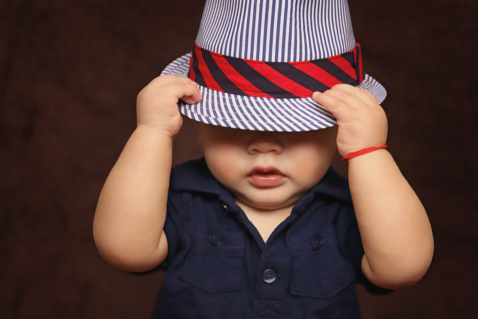 A young boy pulling a hat over his face