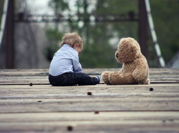 A toddler sitting next to a teddy bear