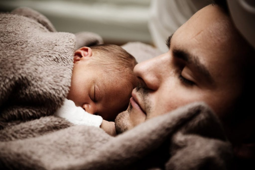 a father with his baby lying on his chest
