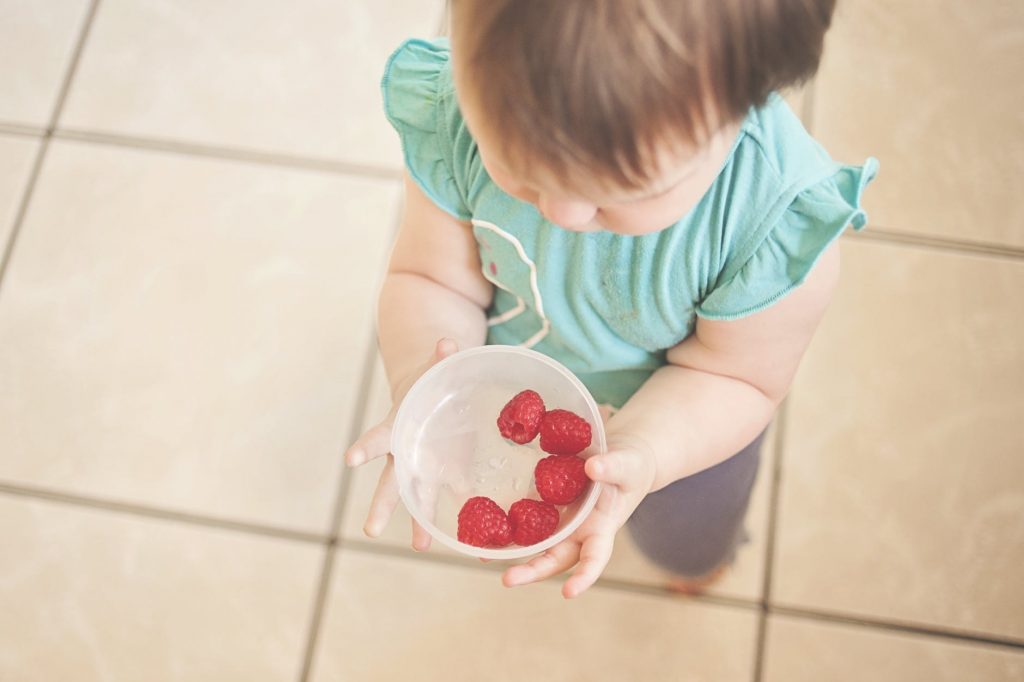 A little girl looking into a bowl with fruit in it