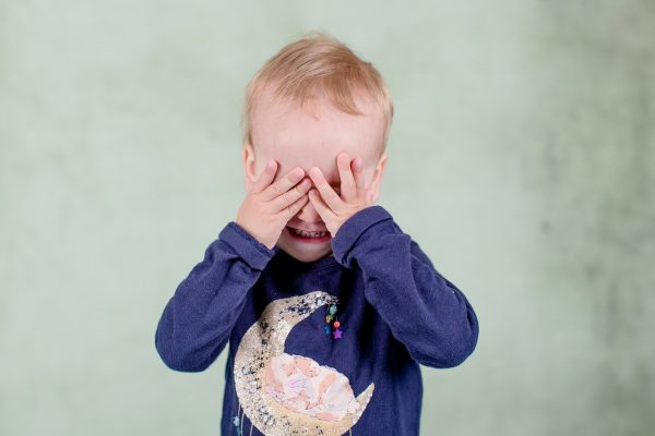 a little boy covering his eyes with his hands