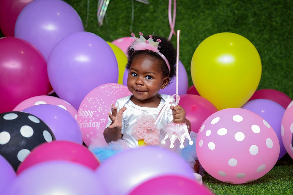 A little girl sitting among birthday balloons