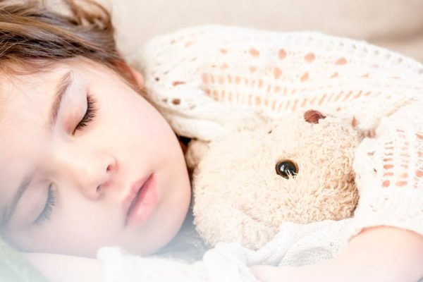 a girl sleeping with a teddy