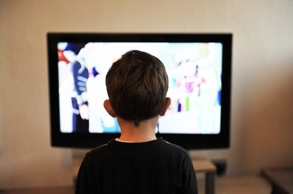 A young boy staring at a tv screen