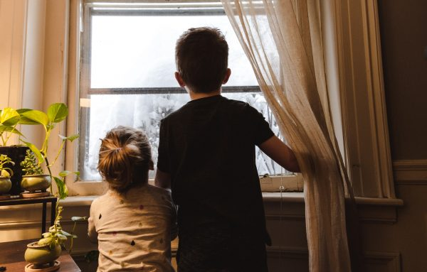 two boys at home looking out the window