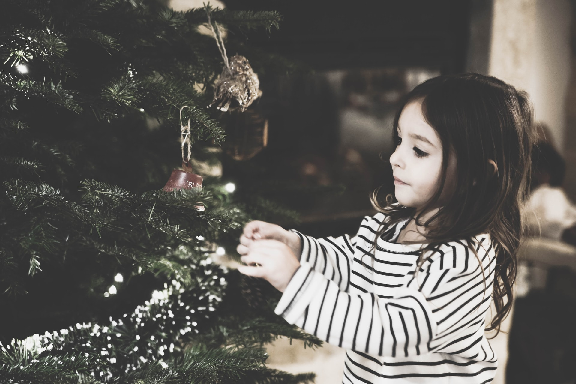 a little girl decorating the Christmas tree to represent how to be happy this christmas