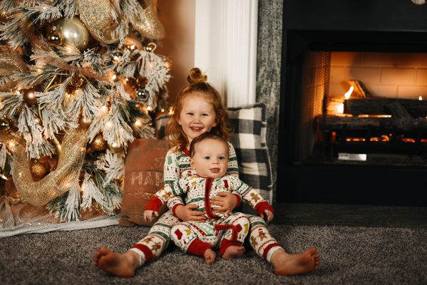 two children posing by a christmas tree to represent how to be happy this christmas