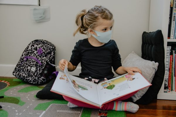 a little girl in school wearing a covid mask to represent parents dealing with separation anxiety