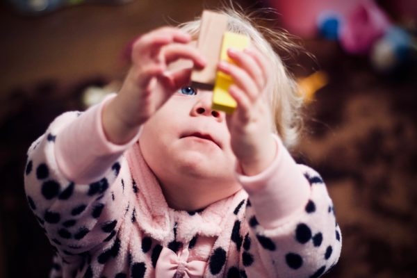 a little girl playing with two building blocks to represent learning at home